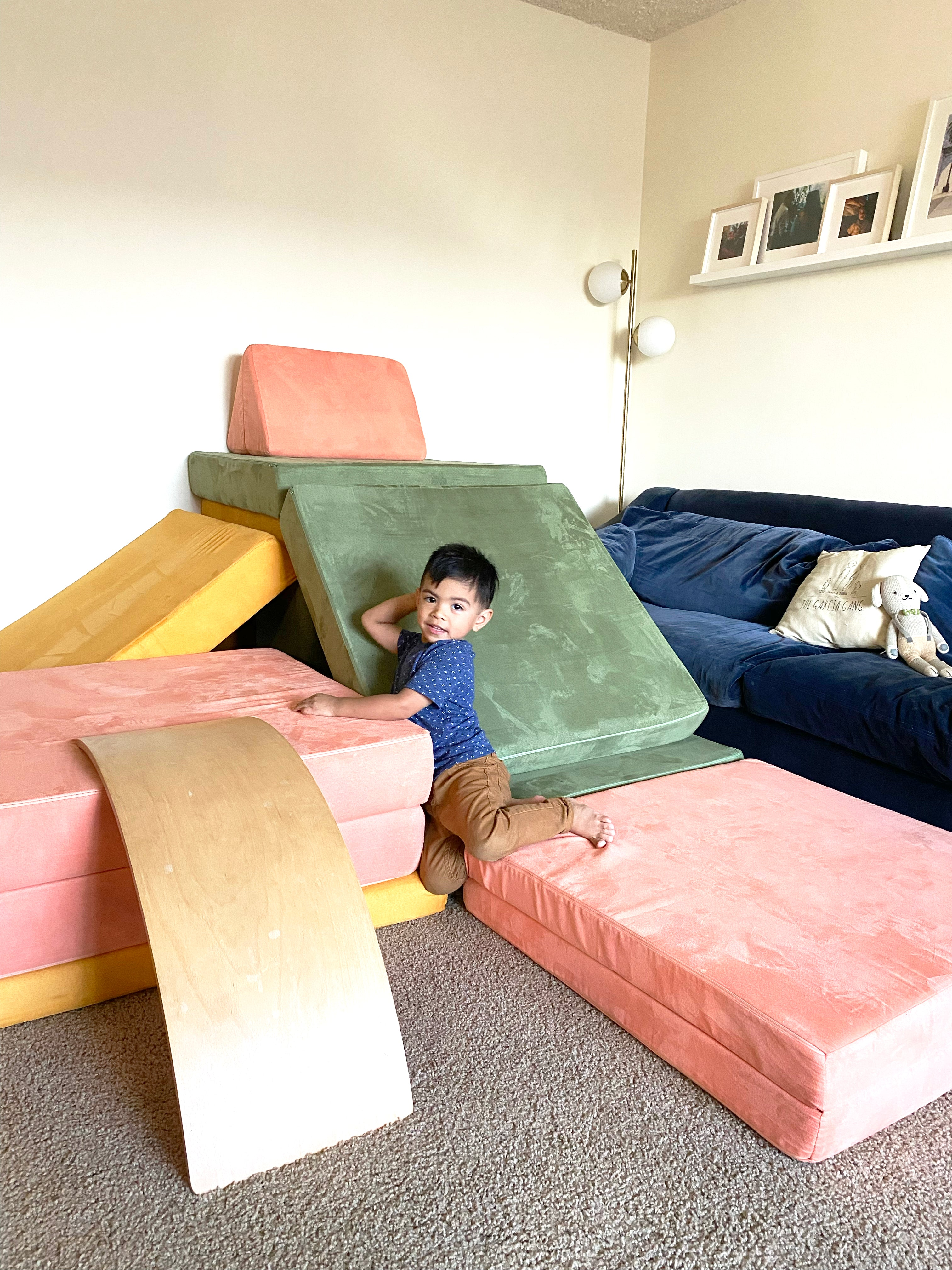 Child sitting on a three-Nugget build, with a slide, ramp to climb up, and lots of fun to be had