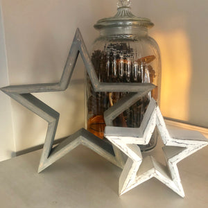 Set of grey and white chunky wooden stars. Large star is grey and smaller star is white, shown with jar full of pine cones and orange slices.