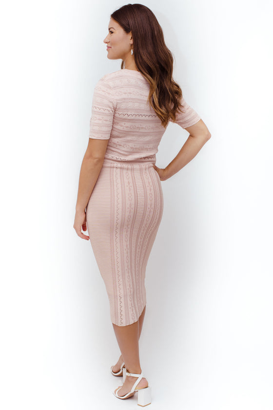 Back Image: fitted light pink, midi dress, high neckline, t-shirt sleeves, stretchy material, flattering on various body types.
