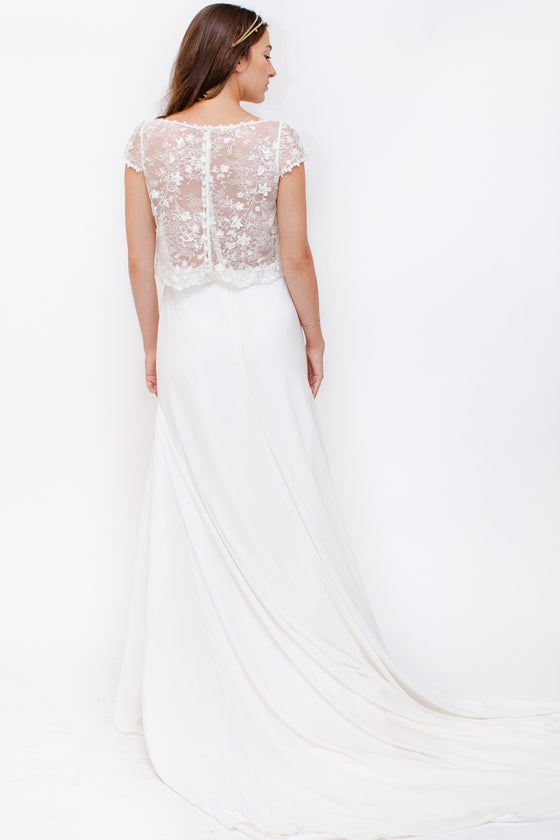 Back Image: high neckline, sheer lace top, with simple skirt and train.  Brand Alma