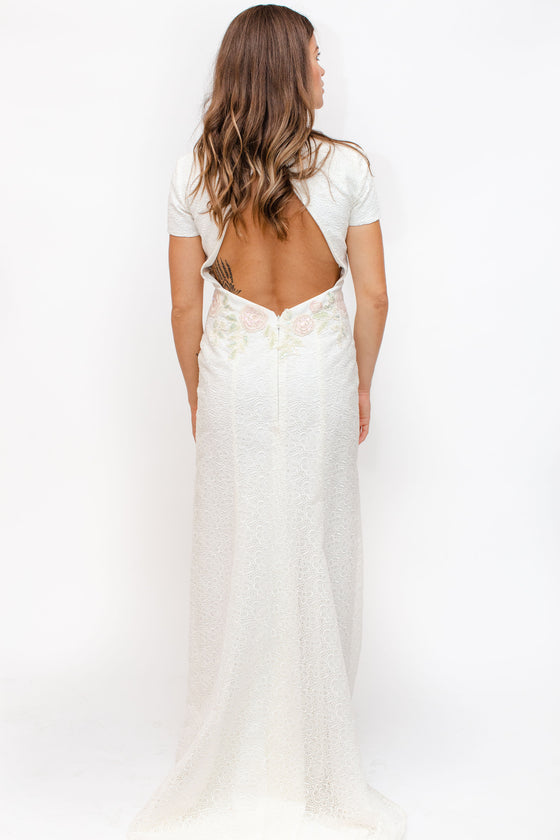 Back Image: large key hole opening, short sleeve wedding dress fitted and floor length with short train. Brand Rembo