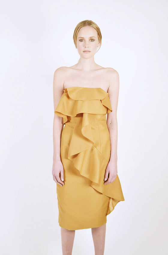 Front Image: straight cut neck line, amber coloured knee length dress, with large front layered frills. Brand Keepsake.