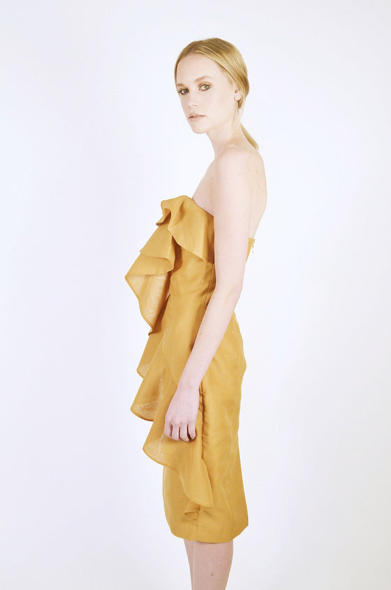 Side Image: straight cut neck line front and back, amber coloured knee length dress, with large front layered frills on front. Brand Keepsake.