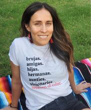 Load image into Gallery viewer, Indigenous woman with long brown hair, smiling and sitting on a color striped sarape, wearing red earrings and a white t-shirt with black lettering, reading brujas. amigas. hijas. hermanas. aunties. visionaries. and with coral pink lettering reading women of color.
