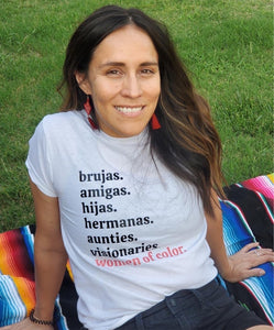Indigenous woman with long brown hair, smiling and sitting on a color striped sarape, wearing red earrings and a white t-shirt with black lettering, reading brujas. amigas. hijas. hermanas. aunties. visionaries. and with coral pink lettering reading women of color.