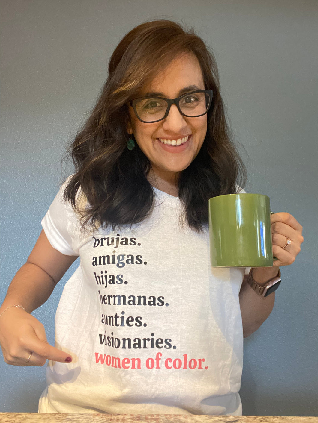 Woman of color with brown hair and glasses, holding a green mug wearing a white t-shirt with black lettering, reading brujas. amigas. hijas. hermanas. aunties. visionaries. and with coral pink lettering reading women of color.