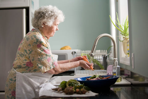 Elderly woman washing vegetables in a flowery dress