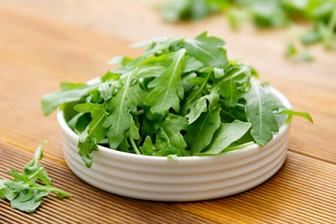 White bowl of baby arugula