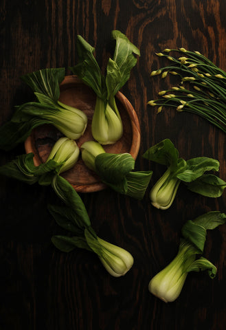 Bok choy in a wooden bowl in evening light