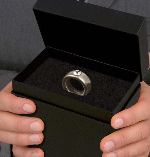 Two hands present a black box with lid removed to reveal a diamond ring inside