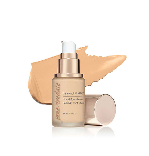 A 0.9-ounce bottle of Jane Iredale Beyond Matte Liquid Foundation in the shade M6 with cap removed and product swatch in the background.