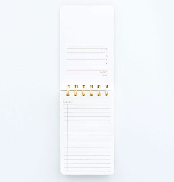 Open notepad showing lined pages and gold wire binding