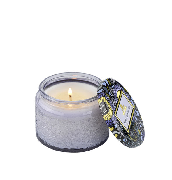Embossed periwinkle candle glass with matching decorative tin lid to the side