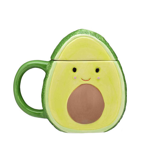 An avocado-shaped mug with domed lid, smiling face, and pit design.