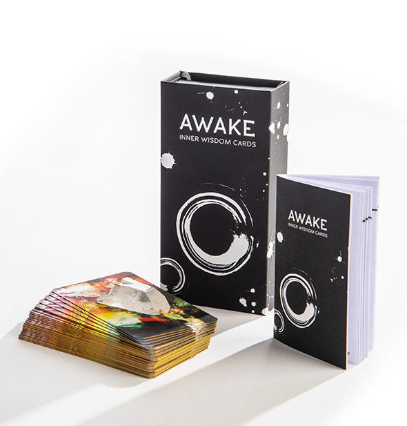 "A rectangular black box with white graphics and the words, ""Awake Inner Wisdom Cards"" sits alongside a booklet of the same design and a colorful card deck with clear crystal on top."