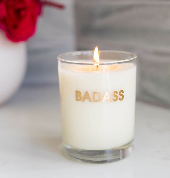 "A burning candle printed with the word ""Badass"" in metallic gold foil."