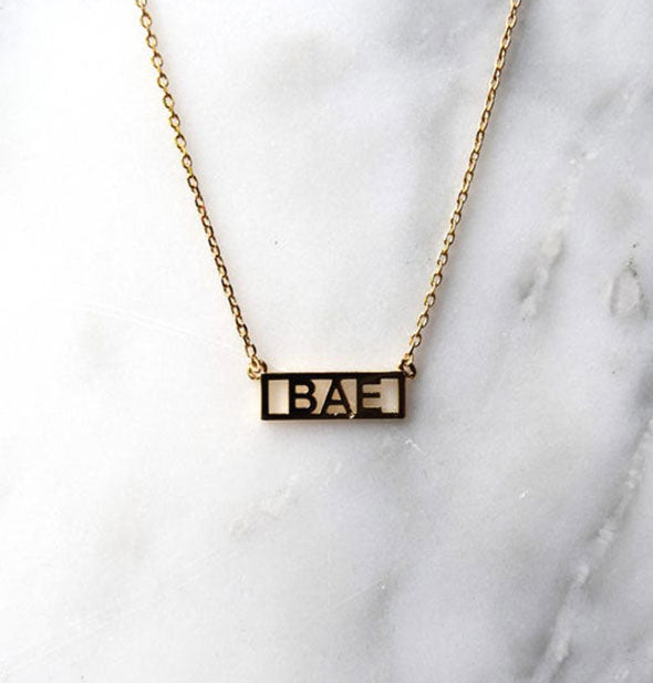 Gold BAE bar becklace on marble background