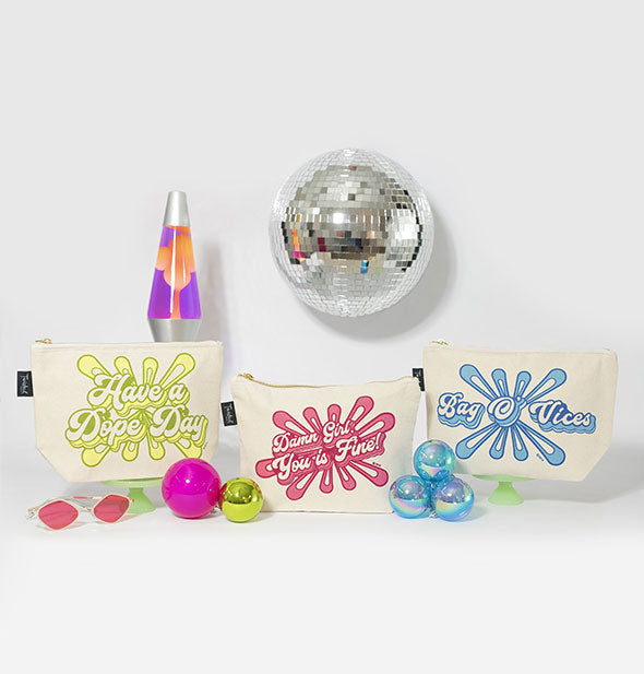 Grouping of retro-style canvas cosmetic pouches with lava lamp, disco ball, and other props