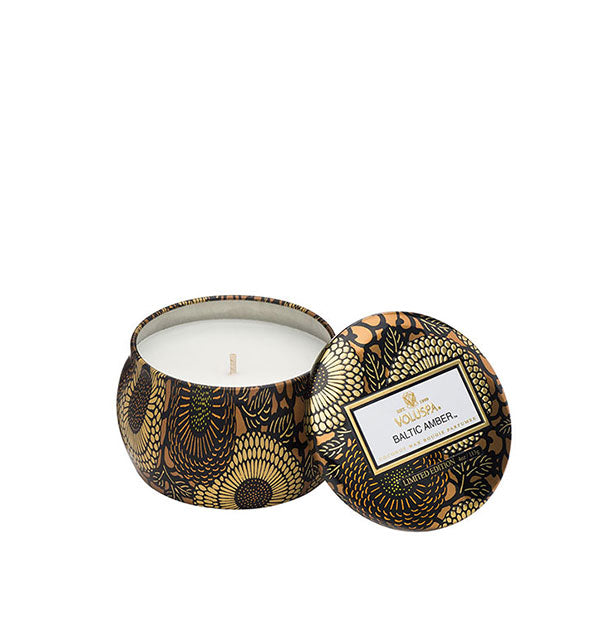A small unlit candle inside a rounded tin with metallic floral design and matching lid set to the side.
