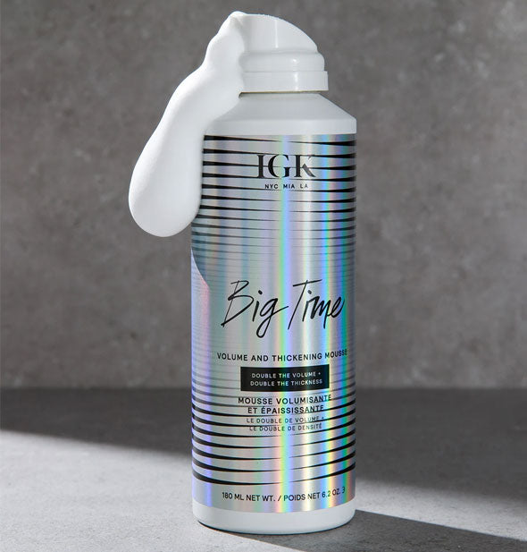 Can of IGK Big Time Volume and Thickening Mousse on a gray marble background with some foamy white product dispensed