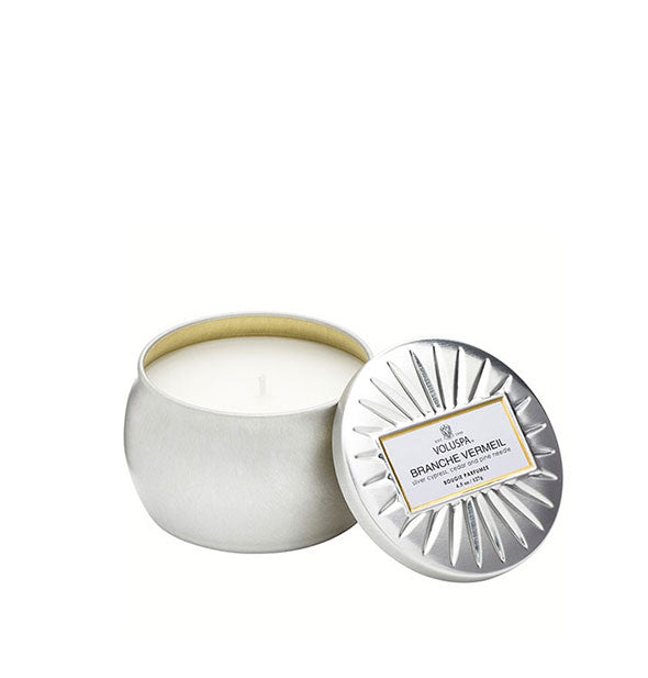 A small unlit candle inside a rounded tin with metallic silver finish and matching embossed lid set to the side.