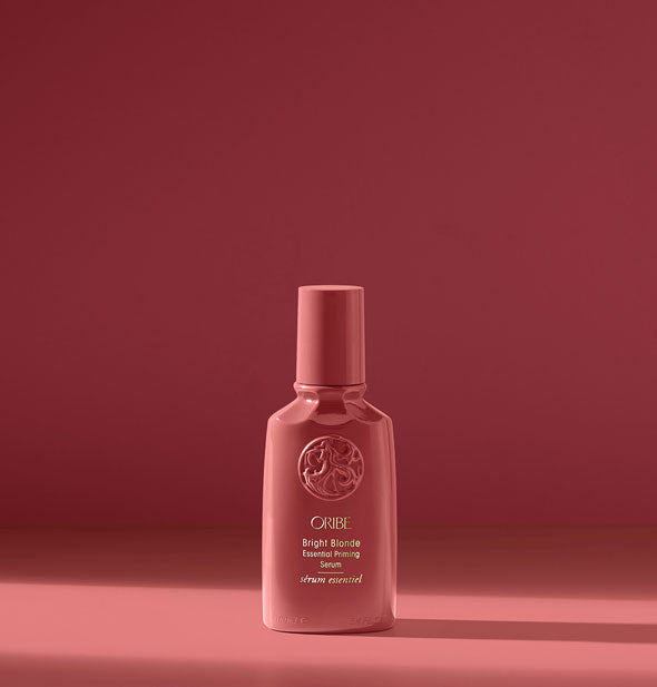 Dark pink bottle of Oribe Bright Blonde Essential Priming Serum on dark pink background