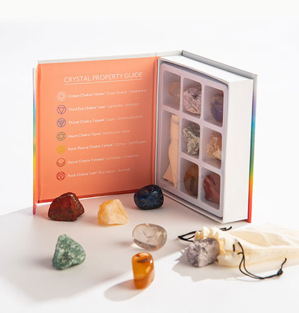 A collection of colorful stones sits in front of an upright, opened box containing more stones and a printed Crystal Property Guide.