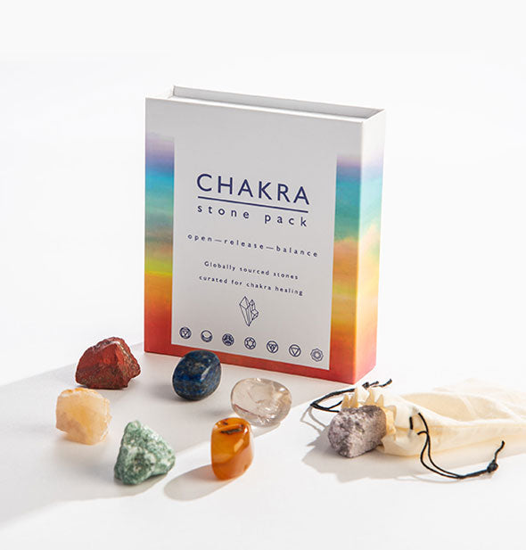 "An arrangement of colorful stones with muslin drawstring bag to the side sits alongside an upright box that says, ""Chakra Stone Pack."""