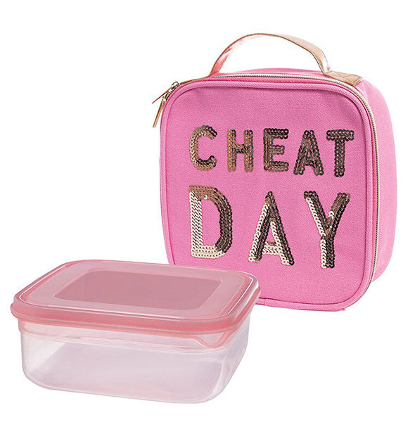 "Pink canvas ""Cheat Day"" lunch bag with gold sequined lettering and handle sits next to accompanying plastic food container"