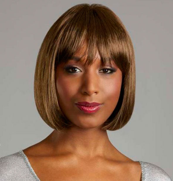 Model wearing a short, medium brown wig with bangs.