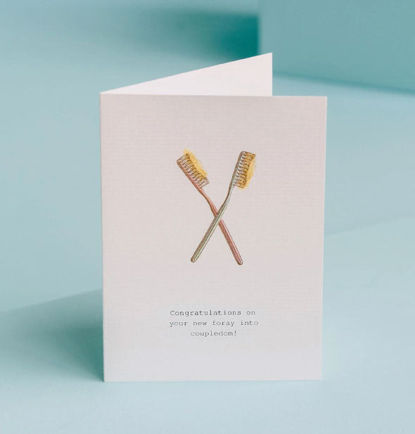 "White greeting card with two toothbrushes illustration says, ""Congratulations on your new foray into coupledom!"""
