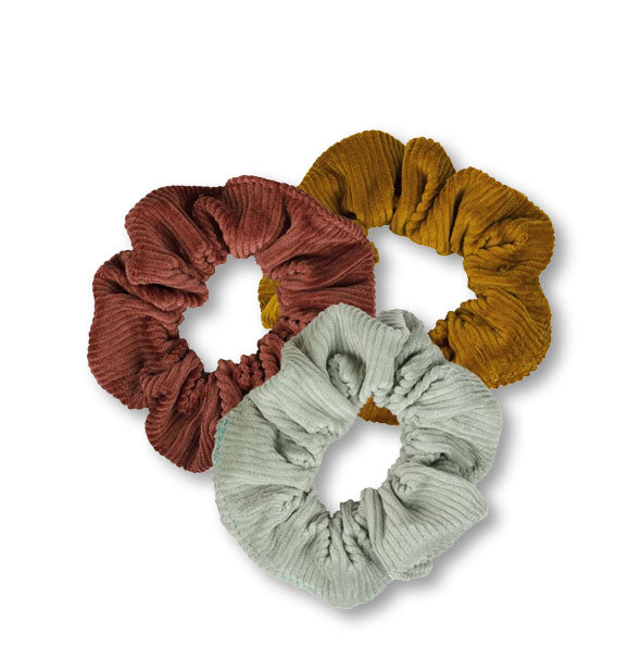 Three corduroy hair scrunchies in dark brown, light brown, and gray