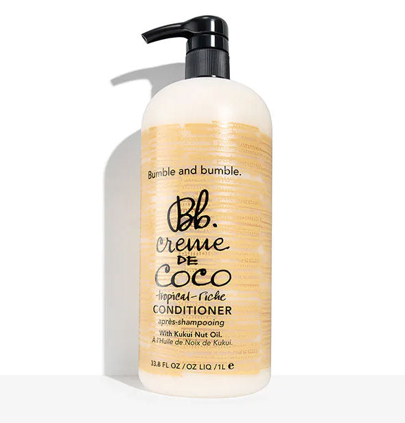 A 33.8-ounce (1 liter) bottle of Bumble and bumble Creme de Coco Tropical-Riche Conditioner with black pump nozzle and brown patterning.