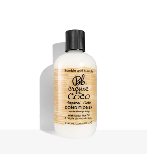 An 8.5-ounce bottle of Bumble and bumble Creme de Coco Tropical-Riche Conditioner with black cap and brown patterning.