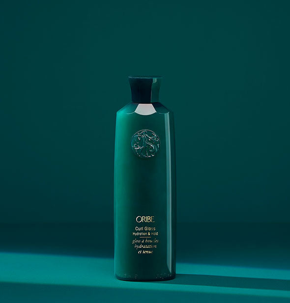 Teal bottle of Oribe Curl Gloss: Hydration & Hold on matching background