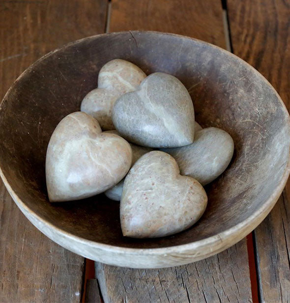 A bowl of Decorative Soapstone Hearts on wooden surface