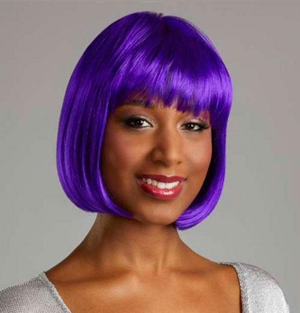 Model wearing a short, purple wig with bangs.