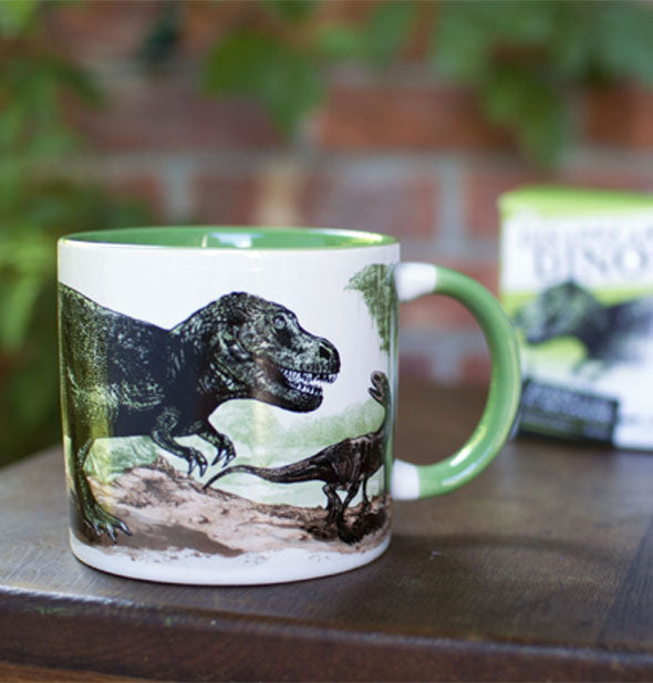 Dinosaur mug on a wooden tabletop with gift box behind