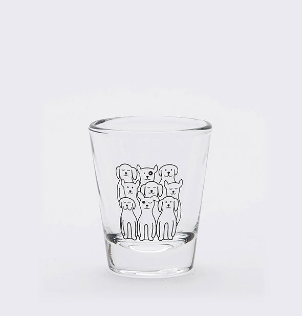 Clear shot glass is printed with black outline drawing of nine dogs, each different.