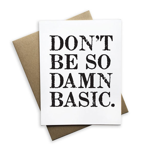 "A white greeting card printed with the words, ""Don't Be So Damn Basic."" in black ink rests on top of a kraft paper envelope."