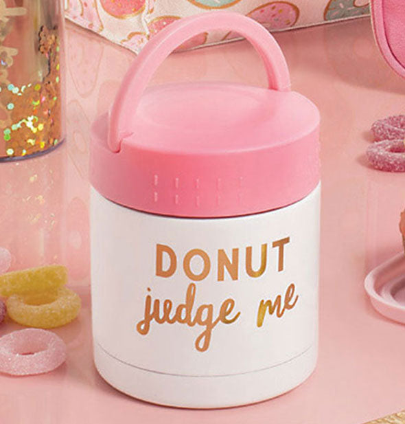 Pink and white bucket-style food container with gold DONUT Judge Me lettering on a decorative pink background