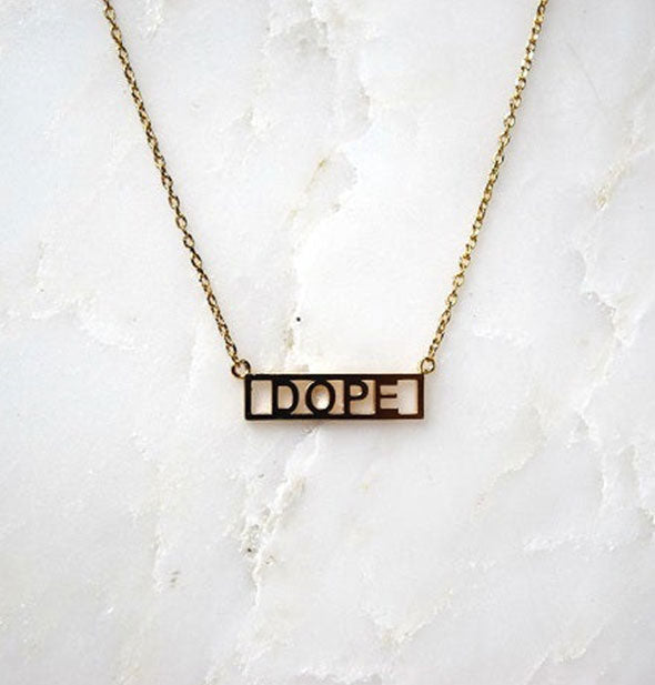 Gold DOPE bar necklace on marble background
