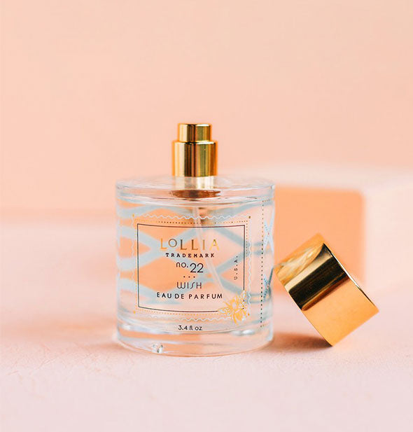 Bottle of Lollia Wish Eau de Parfum on pink background.