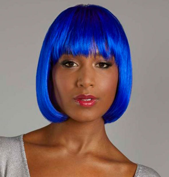 Model wearing a short, bright blue wig with bangs.
