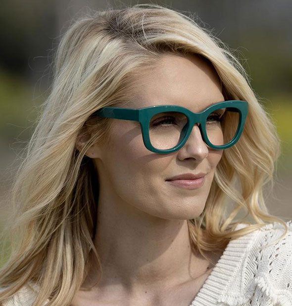 A model wears Peepers Center Stage Readers in Emerald.
