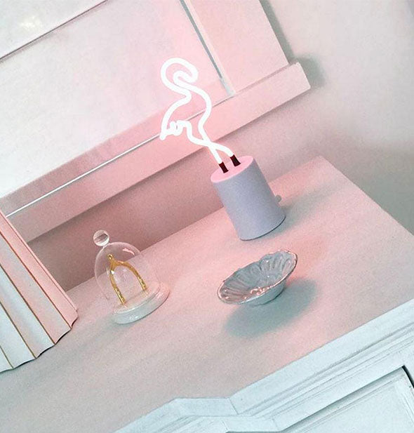 A lit pink flamingo neon light sits atop a white chest of drawers among other knickknacks and collectibles.