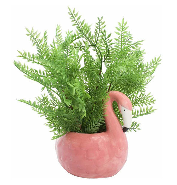 A green fern-like plant sits in a ceramic pot shaped and painted to resemble a pink flamingo.