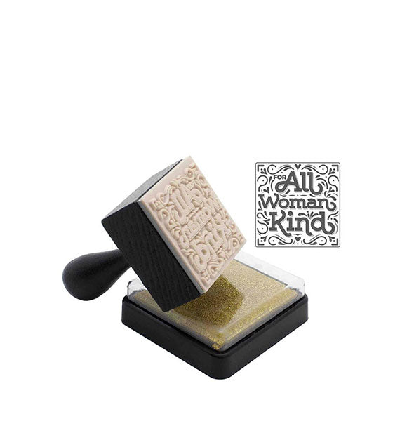 "Stamper with handle sits angled atop an ink pad with sample stamping to the right that reads, ""For All Woman Kind."""