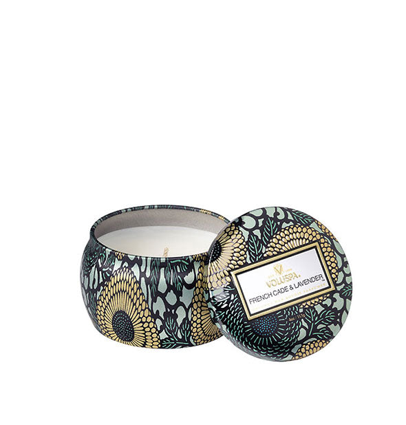 A small unlit candle inside a rounded tin with blue and gold metallic floral design and matching lid set to the side.