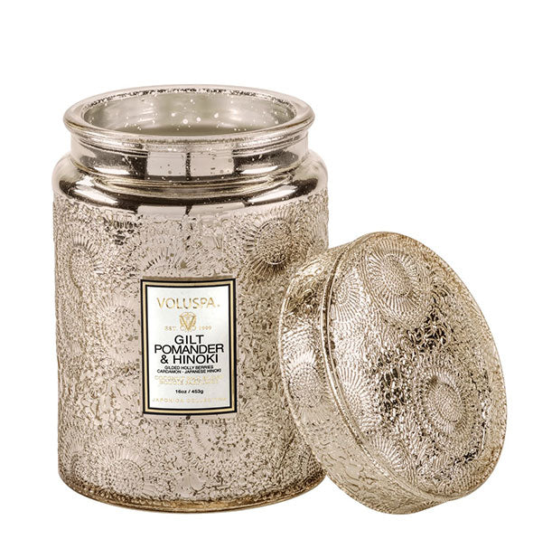 Metallic finish candle jar with lid set to the side